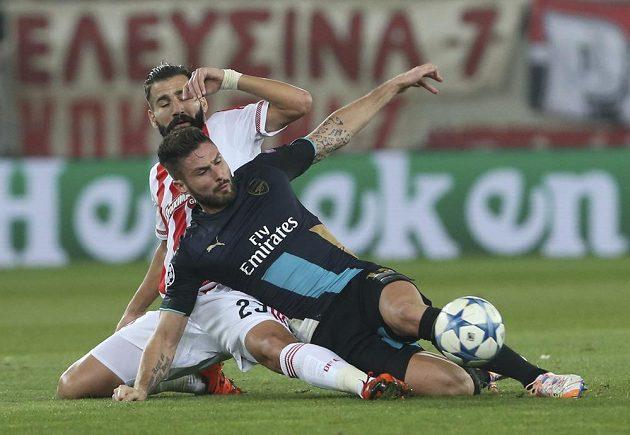 Útočníka Arsenalu Oliviera Girouda (vpravo) se snaží obrat o míč Dimitris Siovas z Olympiakosu.