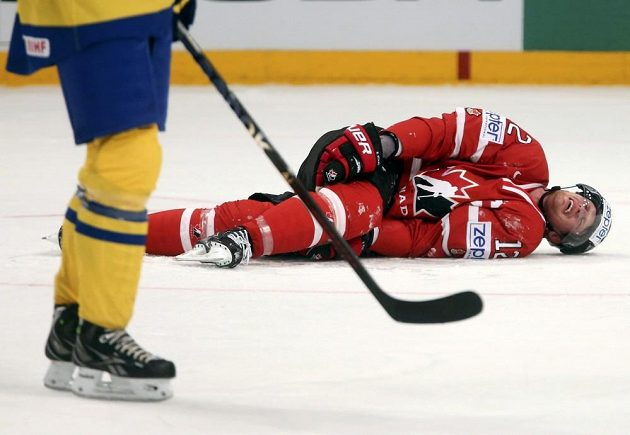 Kapitán kanadské hokejové reprezentace Eric Staal (vpravo) se na ledě svíjí v bolestech po zákroku švédského obránce Edlera.