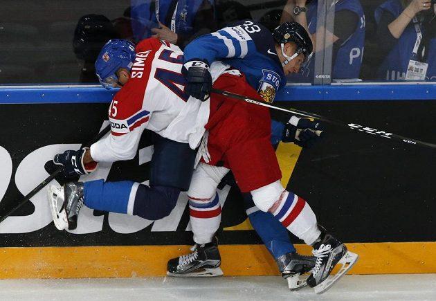 Obránce české hokejové reprezentace Radim Šimek v tvrdém střetu u mantinelu s Finem Markusem Hannikainenem během utkání mistrovství světa v Paříži.