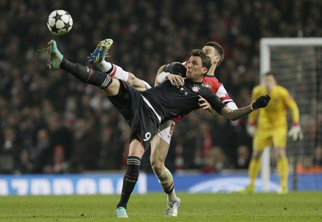 Mario Mandžukič (vlevo) z Bayernu v akrobatickém souboji s Laurentem Koscielnym z Arsenalu.