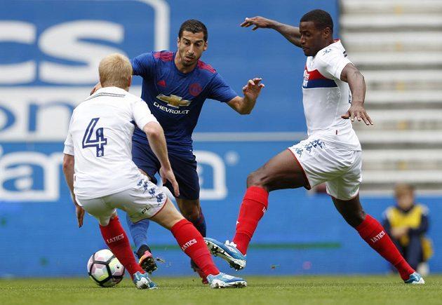Posila v dresu Manchesteru United Henrich Mchitarjan (uprostřed) v akci při zápase ve Wiganu.