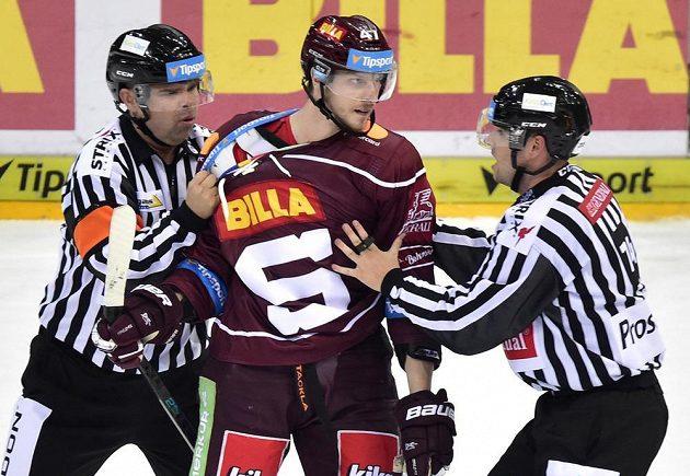 Rozhodčí uklidňují hokejistu Jana Buchteleho ze Sparty v utkání se Zlínem.