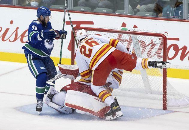 Hokejista Calgary Flames Michael Stone (26) tvrdě narazil do svého spoluhráče Daniela Vladaře v brance Plamenů v přípravném utkání s Vancouverem Canucks.