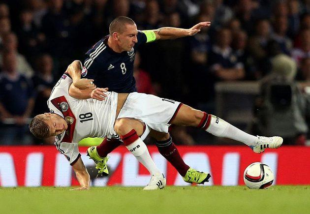 Toni Kroos (dole) z Německa v souboji s kapitánem skotského celku Scottem Brownem.
