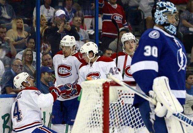Útočník Montrealu Tomáš Plekanec (vlevo) slaví se spoluhráči gól v síti Tampy Bay. Vpravo je brankář Lightning Ben Bishop.