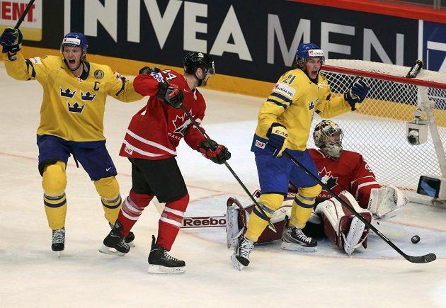 Švéd Nicklas Danielsson (vlevo) slaví gól do branky Kanaďana Mika Smithe.