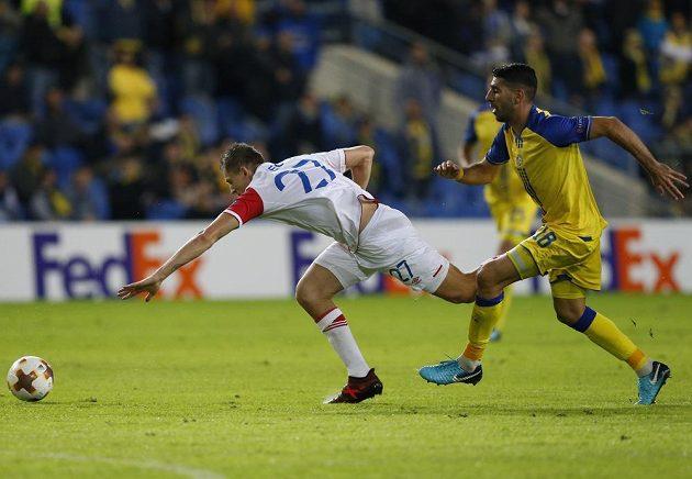 Útočník Slavie Tomáš Necid padá po souboji s Eytanem Tibim z Maccabi Tel Aviv v utkání Evropské ligy.