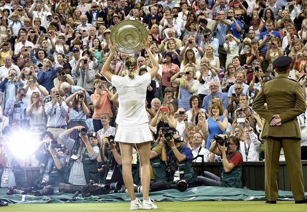 Petra Kvitová pózuje divákům s trofejí pro vítězku Wimbledonu.