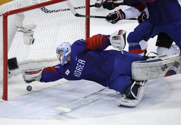 Korejský gólman Matt Dalton se vrhá po puku, který na jeho branku vyslal Švýcar Bois Felicien Du v utkání olympijského turnaje.