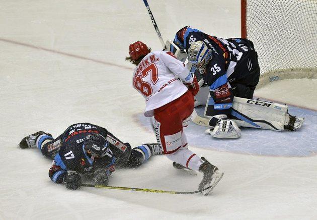 Brankář hokejových Bílých Tygrů Roman Will zasahuje, do šance se dral třinecký útočník Michal Kovařčík, liberecký obránce Lukáš Derner ho neuhlídal.