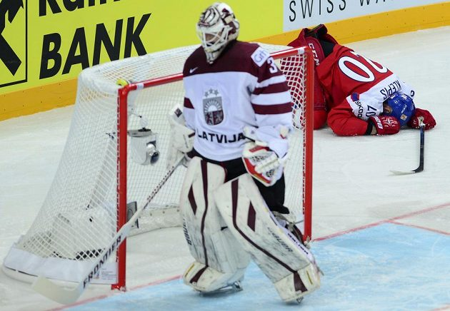 Zraněný Jakub Klepiš v první třetině za lotyšskou brankou, vpředu Edgars Masalskis.