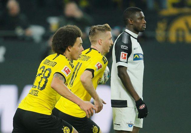 Marco Reus (uprostřed) a Axel Witsel z Dortmundu po vyrovnání na 3:3 proti Paderbornu. Vpravo Jamilu Collins.
