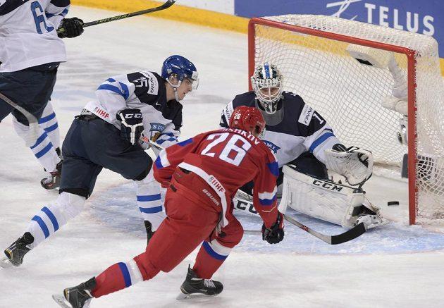 Ruský hokejista Jegor Korškov (uprostřed) se snaží překonat finského brankáře Kaapa Kahkonena během finále MS do 20 let.