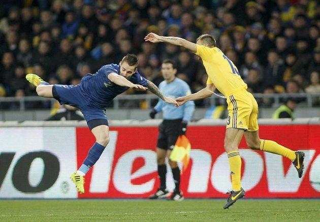 Ukrajinský fotbalista Vjačeslav Ševčuk (vpravo) v souboji s Mathieuem Debuchym z Francie v barážovém utkání o postup na MS.