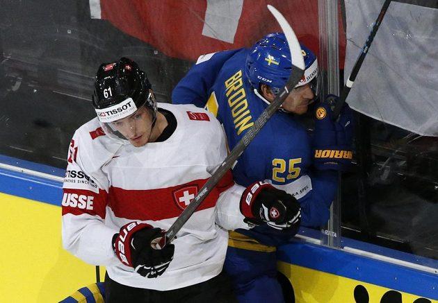 Švýcarský hokejista Fabrice Herzog v souboji u mantinelu se Švédem Jonasem Brodinem během čtvrtfinále mistrovství světa.