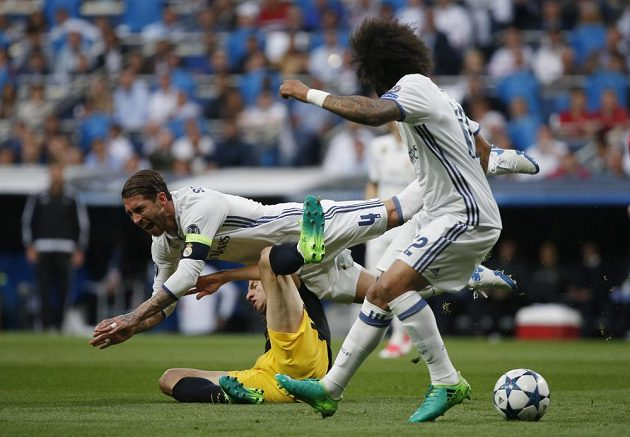 Kapitán Realu Madrid Sergio Ramos padá po souboji s Felipem Luisem z Atlétika v úvodním semifinále Ligy mistrů. Všemu přihlíží obránce Realu Marcelo.