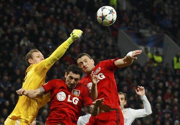 Brankář Bayeru Leverkusen Bernd Leno ve spolupráci s Robertem Hilbertem a Kyriakosem Papadopulosem (zleva) odvrací míč v osmifinále Ligy mistrů proti Atlétiku.
