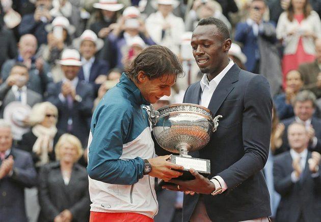 Dvě sportovní legendy - španělský tenista Rafael Nadal dostává trofej pro vítěze French Open od jamajského sprintera Usaina Bolta.