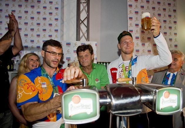 Lukáš Krpálek si na oslavu získané zlaté olympijské medaile dopřál pivo. Vlevo v popředí ho čepuje trenér Petr Lacina, vlevo v pozadí přihlíží ministryně školství Kateřina Valachová.