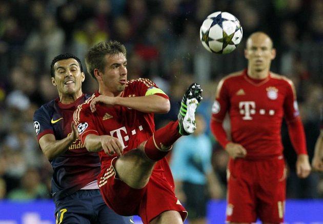 Kapitán Bayernu Philipp Lahm odkopává míč před Pedrem z Barcelony, vzadu přihlíží Arjen Robben.