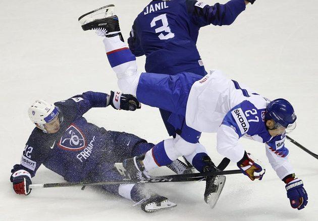 Slovenský hokejový reprezentant Ladislav Nagy padá přes francouzského hokejistu Jordanna Perreta během utkání mistrovství světa.