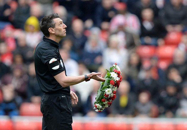 Rozhodčí Lee Probert drží věnec při minutě ticha za oběti tragédie v Hillsborough.