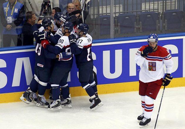 Hokejisté Slovenska slaví vyrovnávací gól proti Česku. Vpravo je smutný obránce Roman Polák.