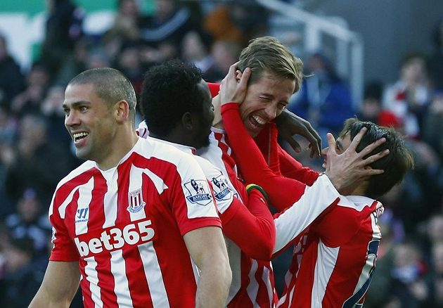 Útočník Stoke City Peter Crouch (uprostřed) a jeho spoluhráči Bojan Krkič (vpravo) a Jonathan Walters (vlevo) slaví gól v utkání proti Arsenalu.
