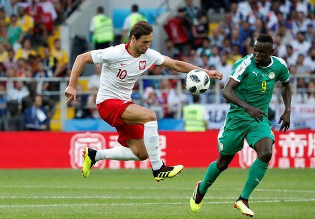 Polský fotbalista Grzegorz Krychowiak v akci, pokouší se v utkání MS obejít senegalského soupeře, kterým byl Mame Biram Diouf.