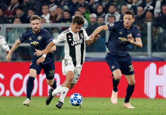 Fotbalista Juventusu Paulo Dybala se snaží prosadit přes duo z Manchesteru United ve složení Luke Shaw - Nemanja Matič.