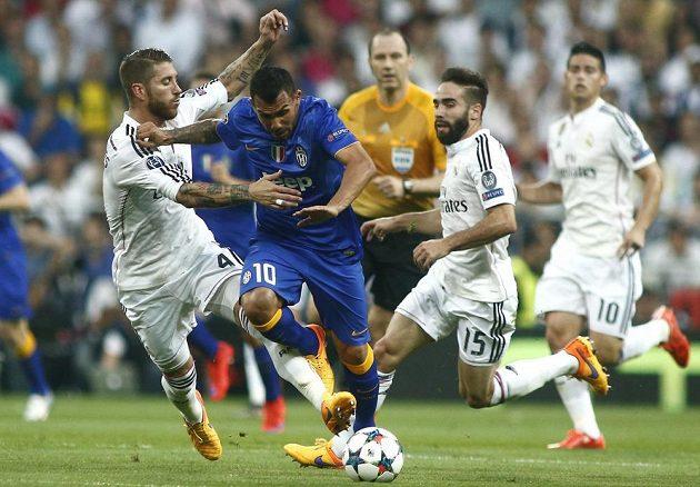 Útočník Juventusu Carlos Tévez (10) prochází přes obránce Realu Madrid Sergia Ramose a Daniho Carvajala (vpravo).