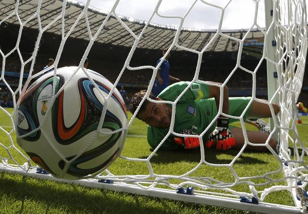 Řecký brankář Orestis Karnezis se smutně dívá za míčem, který mu do sítě šoupl Kolumbijec Pablo Armero.