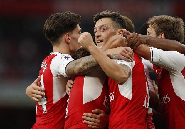 Záložník Arsenalu Mesut Özil (uprostřed) slaví se spoluhráči gól v síti Chelsea.