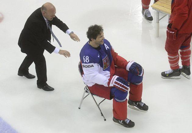Fyzioterapeut Pavel Kolář (vpravo) odváží na židli Jaromíra Jágra po focení týmu na tréninku.