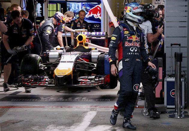 Úřadující šampión Sebastian Vettel (vpravo) zklamaně opouští garáž svého týmu Red Bull.