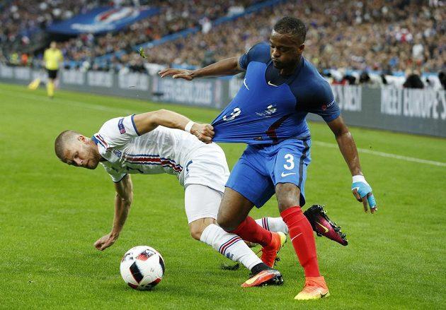 Francouzský zadák Patrice Evra (vpravo) v souboji s Johannem Gudmundssonem z Islandu.