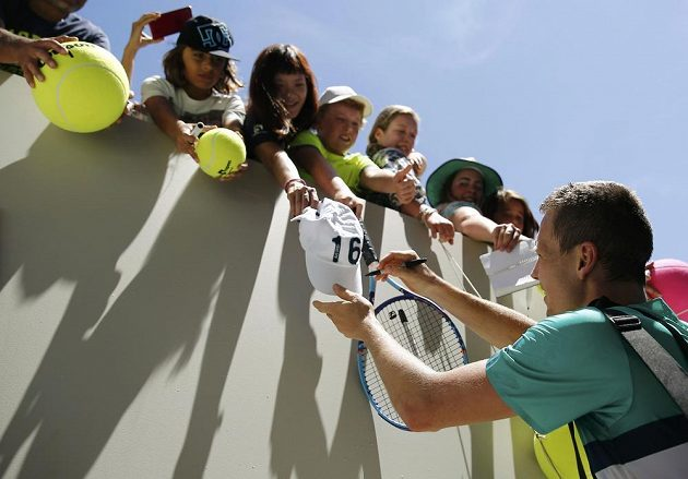 Tomáš Berdych rozdává autogramy fanouškům po vítězném vstupu do grandslamového šampionátu v Melbourne.