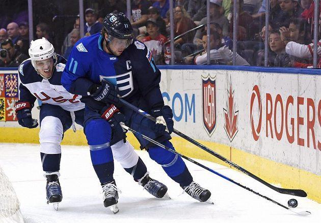 Anže Kopitar z Výběru Evropy (vpravo) a boj o puk s Johnem Carlsonem z USA během utkání Světového poháru.