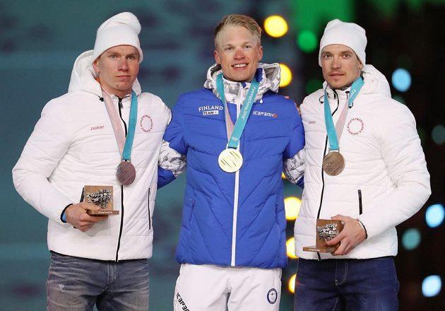 Závěrečné medailové vyhlášení závodu mužů v běhu na lyžích 50 km klasicky proběhl v rámci závěrečného ceremoniálu. Zleva stříbrný Alexander Bolšunov z týmu OSR, vítězný Iivo Niskanen z Finska a třetí Andrej Larkov z týmu OSR.