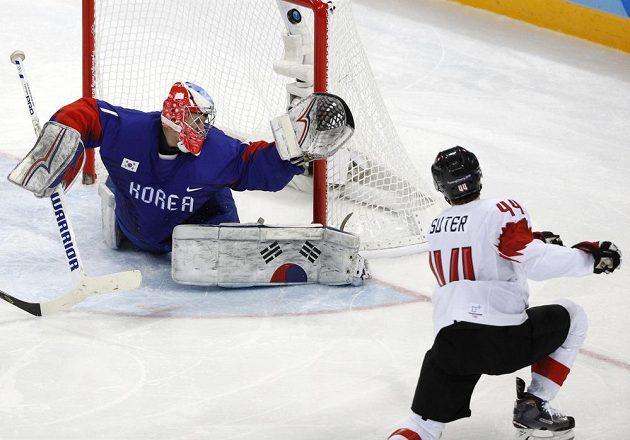 Švýcarský hokejista Pius Suter překonává korejského gólmana Matta Daltona v utkání olympijského turnaje.