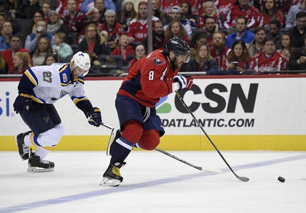 Ruský snajpr Washingtonu Alexandr Ovečkin prchá v utkání proti St. Louis Blues obránci soupeře Alexi Pietrangelovi.