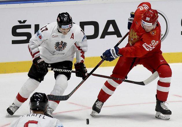 Rakouský hokejista Manuel Ganahl bojuje o puk s Michailem Sergačovem z Ruska v utkání mistrovství světa.