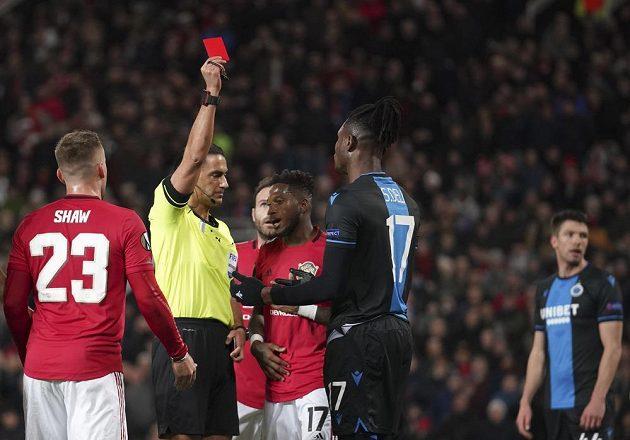 Rozhodčí Serdar Gozubuyuk dává žlutou kartu Simonu Delimu z Brugg v odvetě s Manchesterem United.