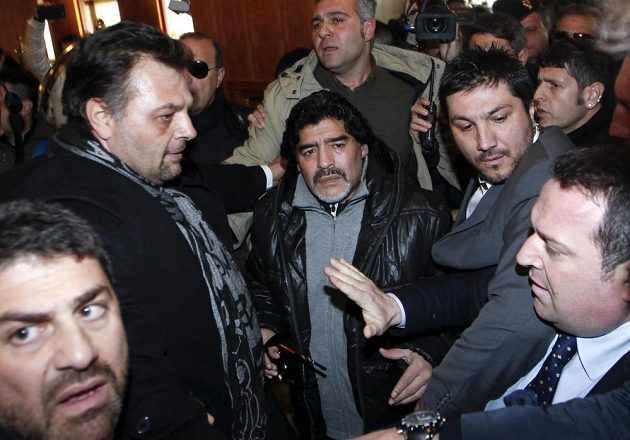 Diego Maradona (uprostřed) v sevření novinářů a bodyguardů.