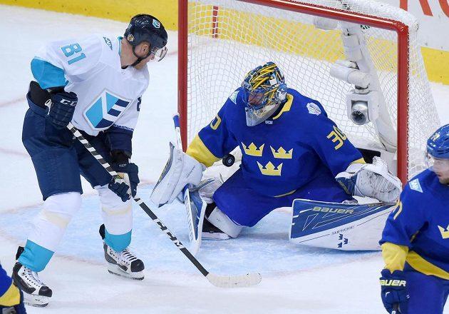 Slovák Marián Hossa se snaží tečovat puk před švédským brankářem Henrikem Lundqvistem.