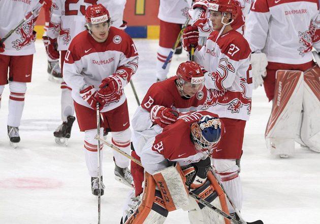 Smutní hokejisté Dánska po čtvrtfinálové porážce s Ruskem. Vpředu je brankář Thomas Lillie.