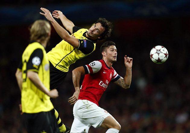 Oliviera Girouda (vpravo), autora vyrovnávací branky Arsenalu, střeží stoper Mats Hummels z Dortmundu.