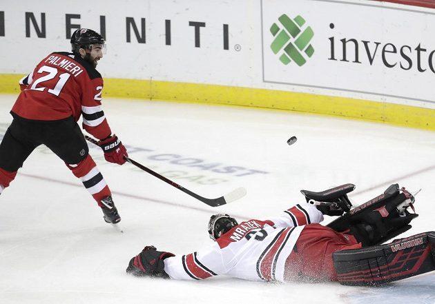 Kyle Palmieri (21) z New Jersey Devils se snaží překonat gólmana Caroliny Petra Mrázka (34) v utkání NHL.