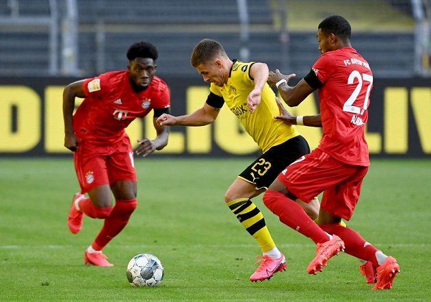 Dortmundský Thorgan Hazard mezi hráči Bayernu. Vpravo David Alaba, vlevo Alphonso Davies.