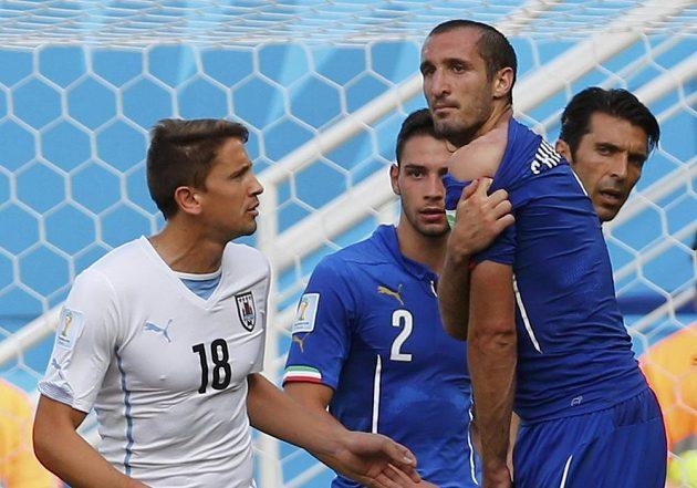 Italský stoper Giorgio Chiellini ukazuje rozhodčímu rameno, kam ho o chvíli dříve kousl uruguayský útočník Luis Suárez.